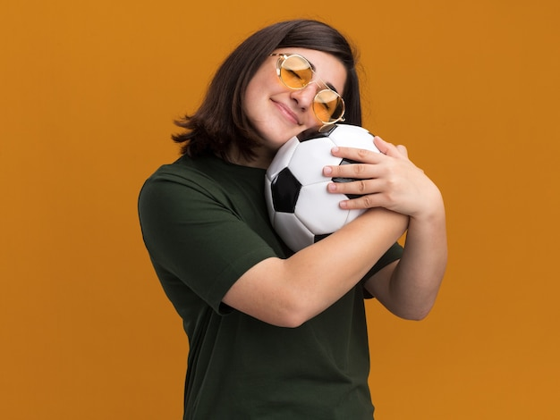 La giovane ragazza abbastanza caucasica piacevole in occhiali da sole abbraccia la palla isolata sulla parete arancione con lo spazio della copia
