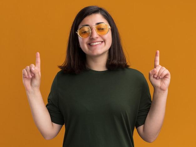 La giovane ragazza abbastanza caucasica contenta in occhiali da sole sta con gli occhi chiusi e punta in alto isolata sulla parete arancione con lo spazio della copia