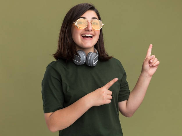 Pleased young pretty caucasian girl in sun glasses and with headphones around neck pointing at side isolated on olive green wall with copy space