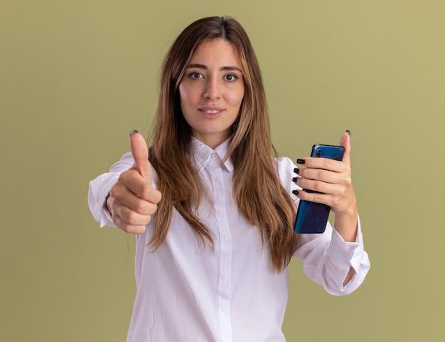 La giovane ragazza abbastanza caucasica soddisfatta alza il pollice e tiene il telefono isolato sulla parete verde oliva con lo spazio della copia
