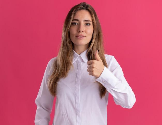 Lieta giovane ragazza abbastanza caucasica pollice in alto isolato sulla parete rosa con spazio di copia