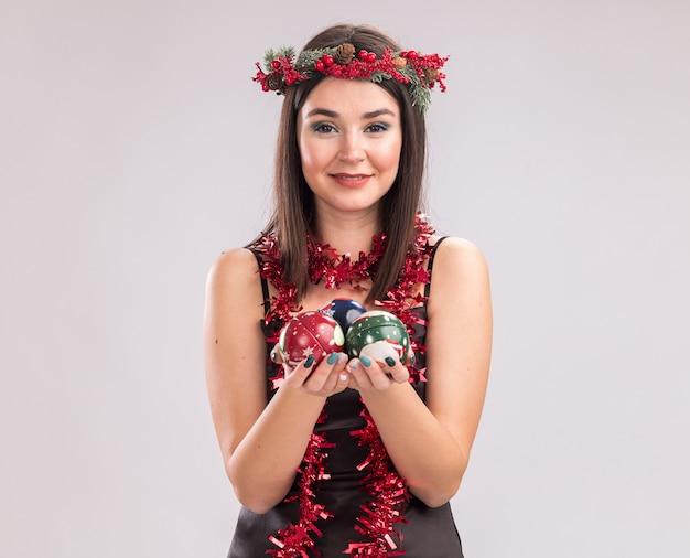 Felice giovane bella ragazza caucasica che indossa la corona di testa di natale e la ghirlanda di orpelli intorno al collo che tiene le palline di natale guardando la telecamera isolata su sfondo bianco con spazio di copia