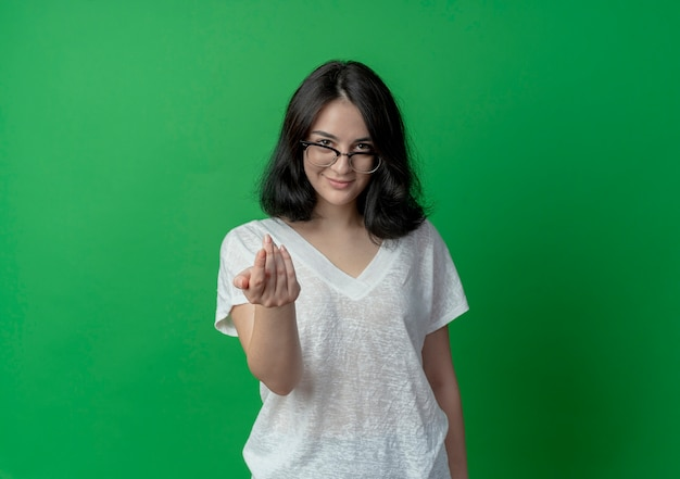 Pleased young pretty caucasian girl wearing glasses doing come here gesture isolated on green background with copy space