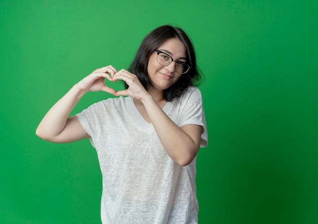 コピースペースで緑の背景に分離されたハートサインをしている眼鏡をかけて満足している若いかなり白人の女の子