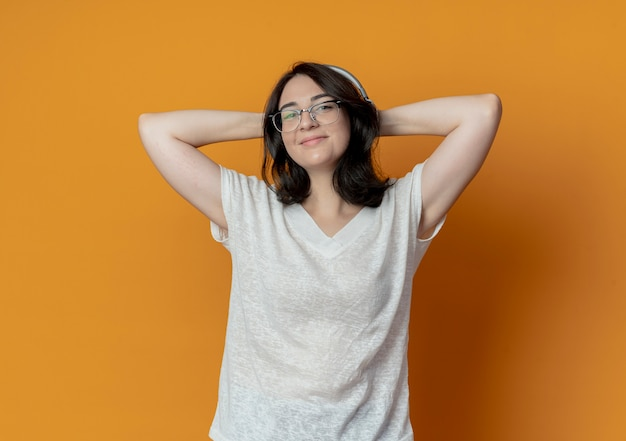 Lieta giovane ragazza piuttosto caucasica con gli occhiali e le cuffie mettendo le mani dietro la testa isolata su sfondo arancione con copia spazio