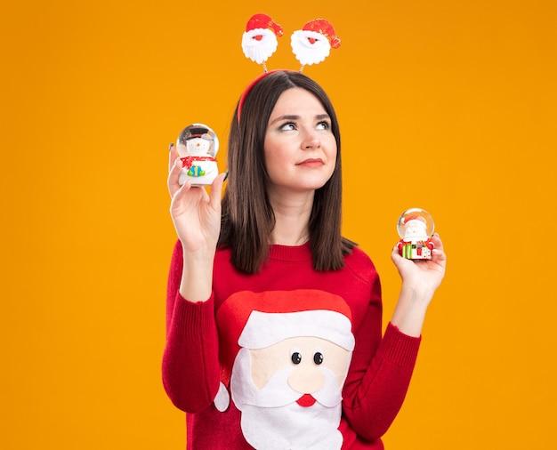 산타 클로스 머리띠와 눈사람과 산타 클로스 인형을 들고 스웨터를 입고 기쁘게 젊은 예쁜 백인 여자 복사 공간이 오렌지 배경에 고립 찾고