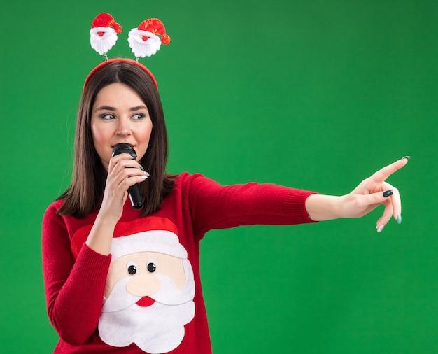 Довольная молодая симпатичная кавказская девушка в свитере санта-клауса и повязке на голове разговаривает в микрофон, смотрит и указывает на сторону, изолированную на зеленой стене
