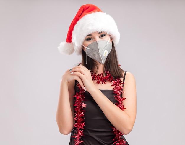 サンタの帽子と保護マスクの見掛け倒しのガーランドを首の周りに身に着けている若いかわいい白人の女の子がコピースペースで白い背景に分離されたハートサインをしているカメラを見て喜んで