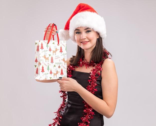 白い背景で隔離のクリスマスギフトバッグを保持しているカメラを見て首の周りにサンタの帽子と見掛け倒しの花輪を身に着けている若いかなり白人の女の子を喜ばせる