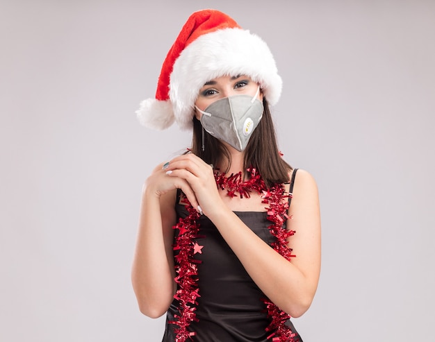 Pleased young pretty caucasian girl wearing santa hat and protective mask tinsel garland around neck looking at camera doing heart sign isolated on white background with copy space