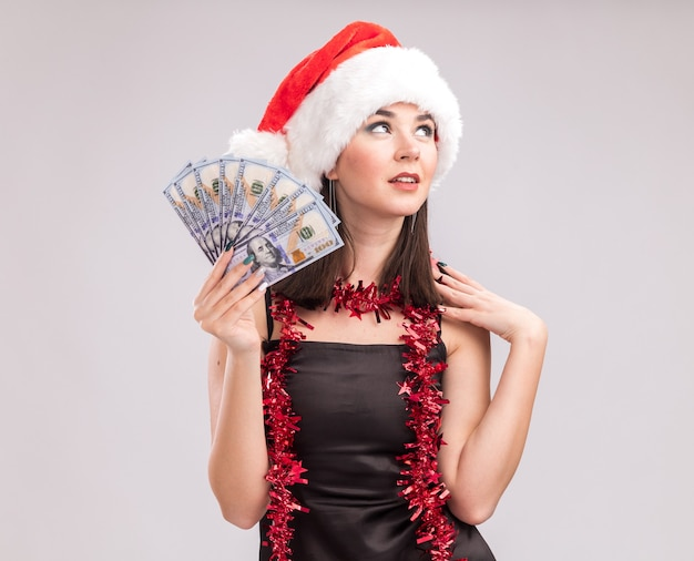 Felice giovane bella ragazza caucasica che indossa un cappello da babbo natale e una ghirlanda di orpelli intorno al collo tenendo i soldi toccando la spalla guardando in alto isolato su sfondo bianco