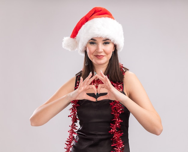 Pleased young pretty caucasian girl wearing santa hat and tinsel garland around neck looking at camera doing heart sign isolated on white background