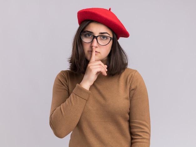 Довольная молодая симпатичная кавказская девушка в берете и в оптических очках делает жест молчания на белой стене с копией пространства