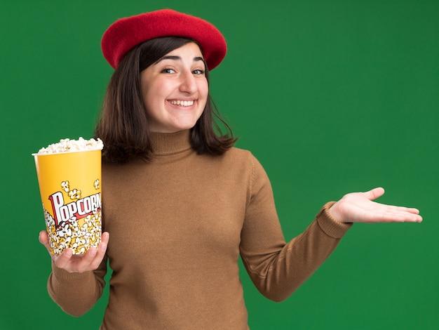 Felice giovane bella ragazza caucasica con berretto che tiene in mano un secchio di popcorn e tiene la mano aperta
