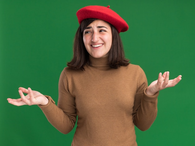 La giovane ragazza abbastanza caucasica piacevole con il cappello del berretto tiene le mani aperte guardando il lato isolato sulla parete verde con lo spazio della copia