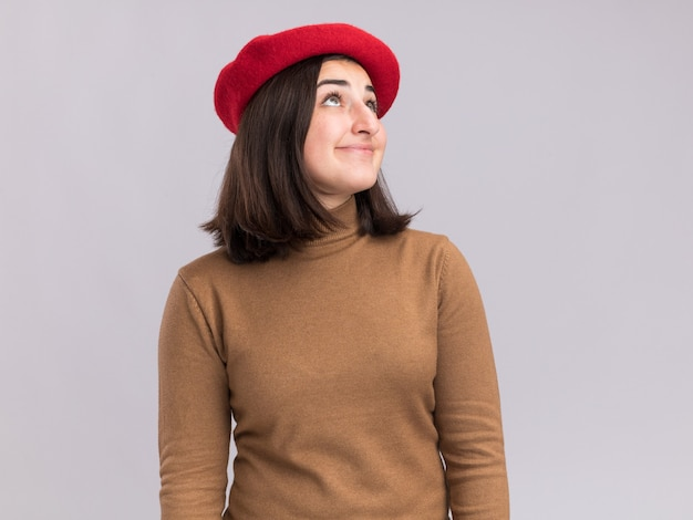 Pleased young pretty caucasian girl with beret hat looking up isolated on white wall with copy space