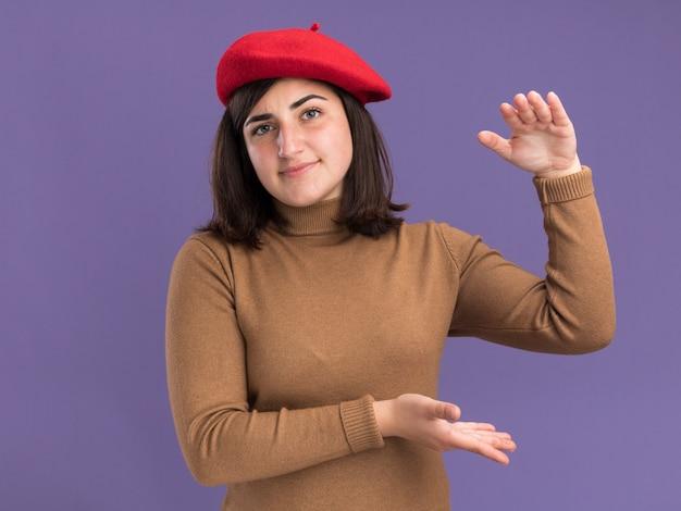 何かを持っているふりをしているベレー帽の帽子をかぶった若いかなり白人の女の子を喜ばせます