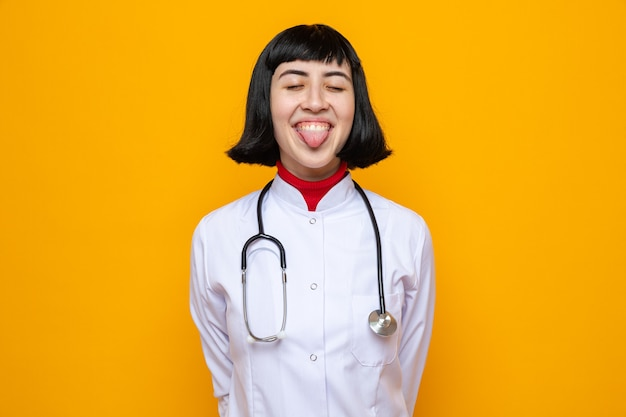 Pleased young pretty caucasian woman in doctor uniform with stethoscope and tongue out standing with closed eyes