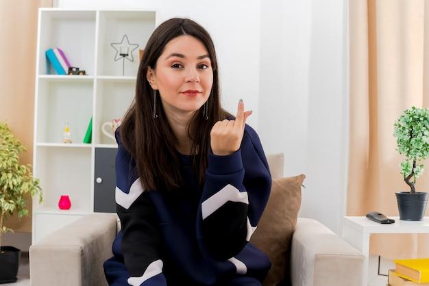Lieta giovane donna abbastanza caucasica seduta sulla poltrona nel soggiorno progettato alla ricerca e facendo gesto di denaro