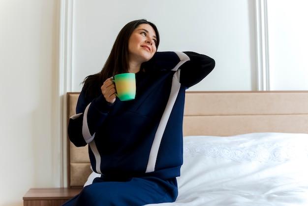 Lieta giovane donna abbastanza caucasica seduta sul letto in camera da letto tenendo la tazza guardando a lato mettendo la mano dietro il collo