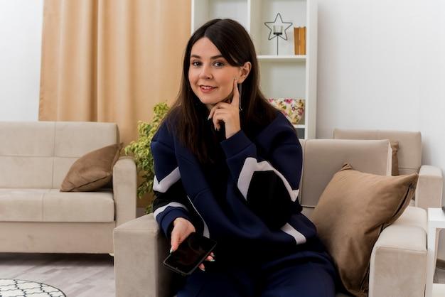 Довольная молодая симпатичная кавказская женщина, сидящая на кресле в дизайнерской гостиной, держит мобильный телефон, трогая лицо пальцем
