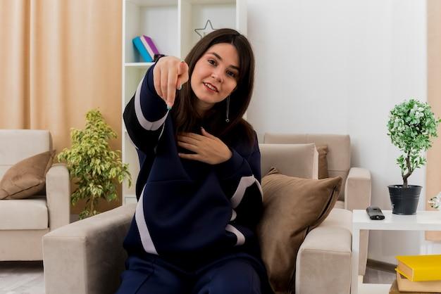 Довольная молодая симпатичная кавказская женщина, сидящая на кресле в дизайнерской гостиной, смотрит, показывает и держит руку на груди