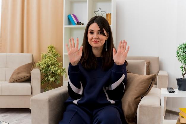 빈 손을 보여주는 설계 거실에서 안락의 자에 앉아 기쁘게 젊은 예쁜 백인 여자