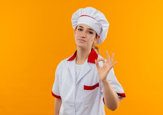 オレンジ色のスペースで隔離されたokサインをしているシェフの制服を着た若いかわいい料理人を喜ばせます
