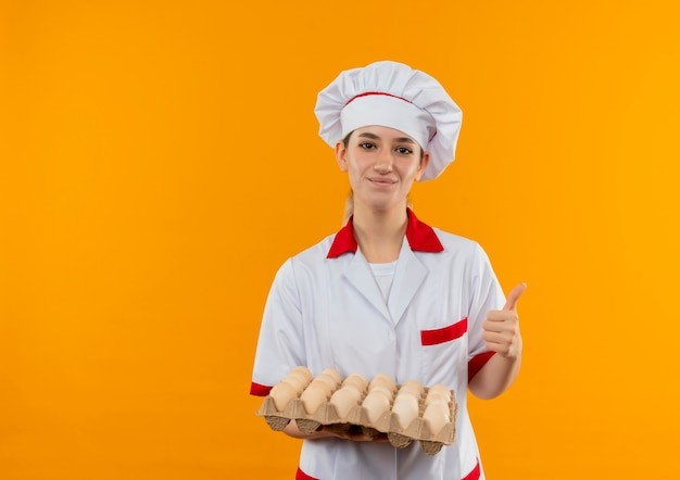 卵のカートンを保持し、オレンジ色のスペースで隔離された親指を見せてシェフの制服を着た若いかわいい料理人を喜ばせる