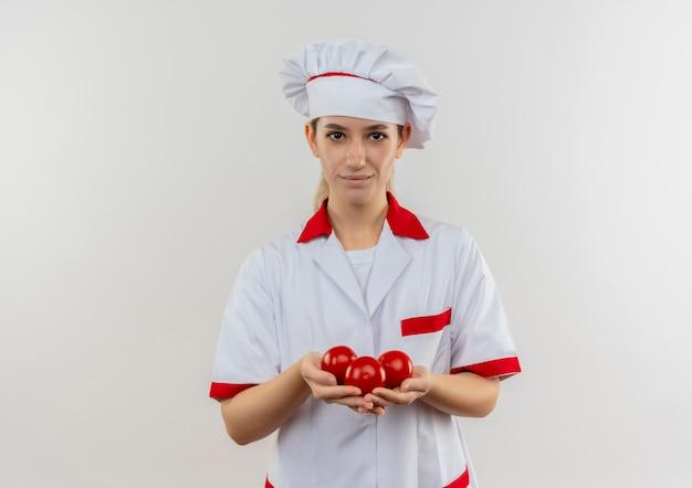 白いスペースに孤立しているように見えるトマトを保持しているシェフの制服を着た若いかわいい料理人を喜ばせる