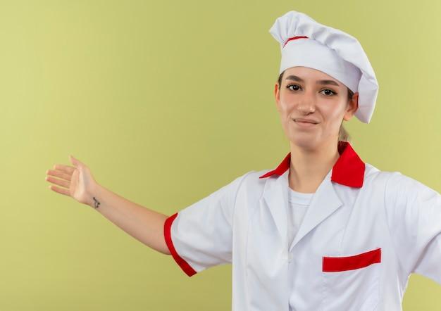 緑地に隔離された開いた腕で見てシェフの制服を着た若いかわいい料理人を喜ばせる