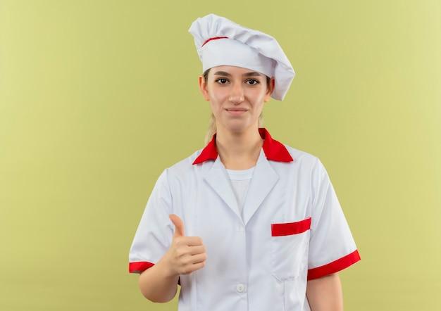 緑地に隔離された親指を見せてシェフの制服を着た若いかわいい料理人を喜ばせる