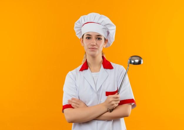 閉じた姿勢で立って、オレンジ色のスペースで隔離された取鍋を保持しているシェフの制服を着た若いかわいい料理人を喜ばせます