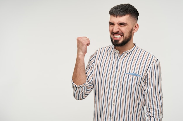 Pleased young pretty dark haired bearded male with short haircut showing happily his teeth and raising fist while looking aside, isolated over white wall