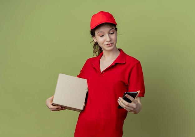Довольная молодая симпатичная доставщица в красной форме и кепке держит картонную коробку и мобильный телефон, глядя на телефон, изолированный на оливково-зеленом фоне с копией пространства