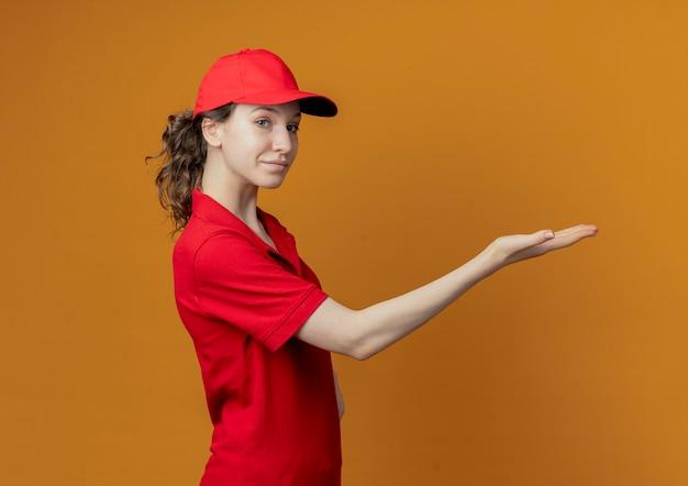Довольная молодая симпатичная доставщица в красной форме и кепке, стоящая в профиле, указывающая прямо рукой и смотрящая в камеру, изолированную на оранжевом фоне с копией пространства