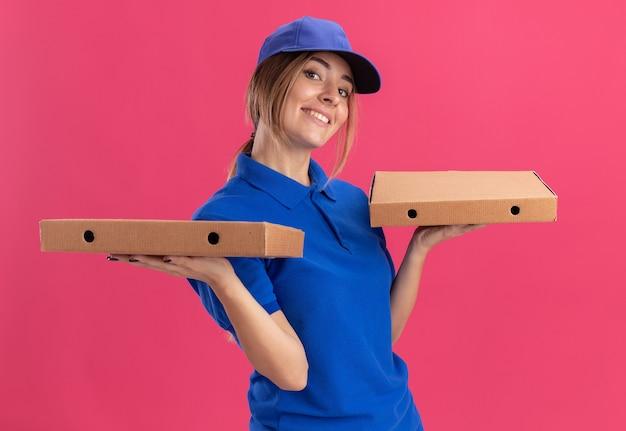 制服を着た若いかわいい配達の女の子がピンクの両手でピザの箱を持って喜んで