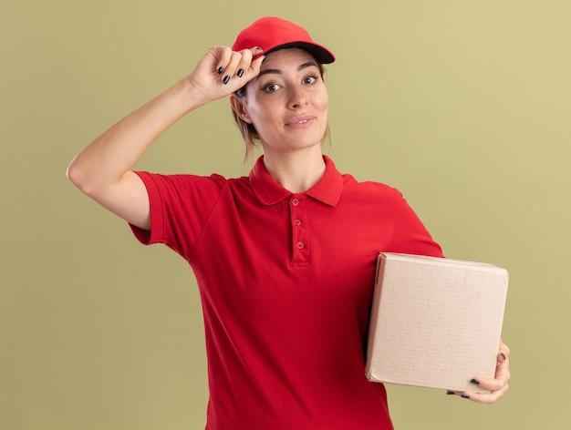 Довольная молодая симпатичная доставщица в униформе кладет руку на кепку и держит картонную коробку на оливково-зеленом