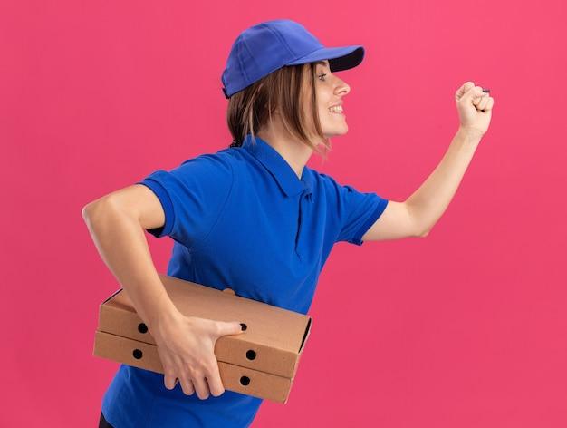 ピンクで走るふりをしてピザの箱を持って横向きに立っている制服を着た若いかわいい配達の女の子を喜ばせます