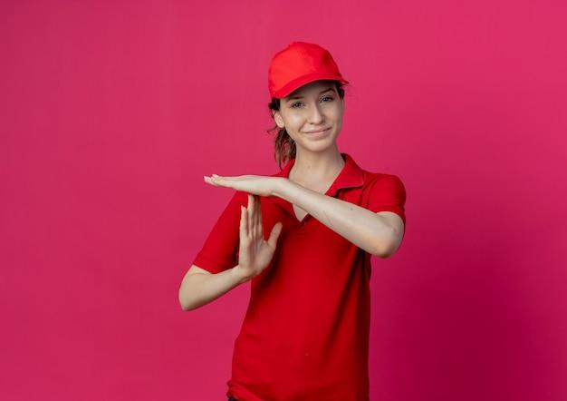 Lieta giovane bella consegna ragazza in uniforme rossa e berretto facendo gesto di timeout isolato su sfondo cremisi con copia spazio