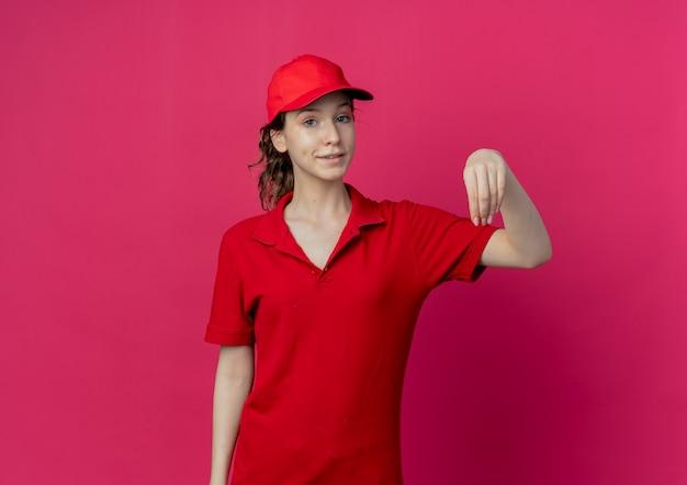 La giovane ragazza graziosa di consegna soddisfatta in uniforme rossa e cappuccio finge che tiene qualcosa