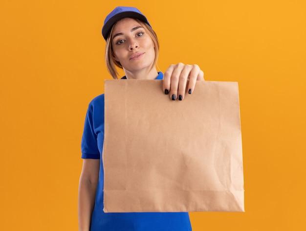 La giovane ragazza graziosa di consegna felice in uniforme tiene il pacchetto di carta sull'arancio