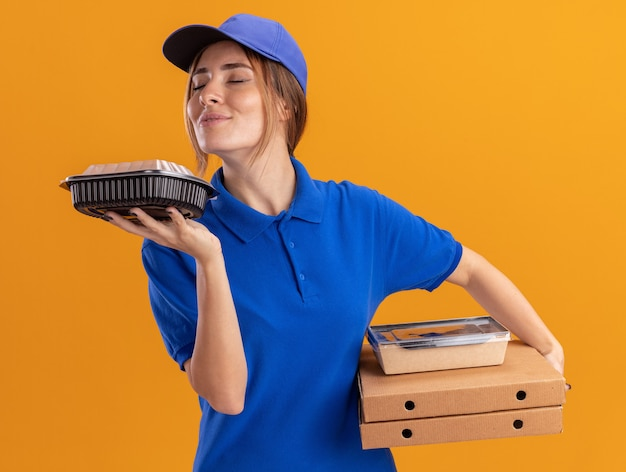 Pleased young pretty delivery girl in uniform holds and sniffs paper food packages containers on pizza boxes on orange