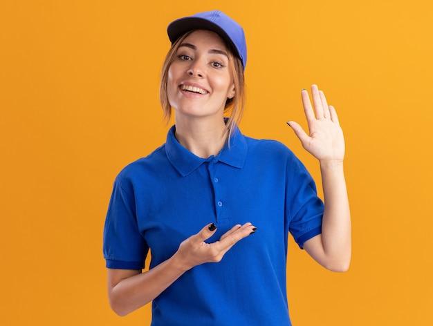 Soddisfatto giovane bella ragazza di consegna in punti uniformi a portata di mano sull'arancio