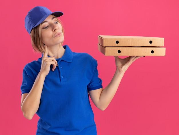 Soddisfatta la giovane bella ragazza delle consegne in uniforme mette il dito sul mento tenendo e guardando le scatole per pizza sul rosa