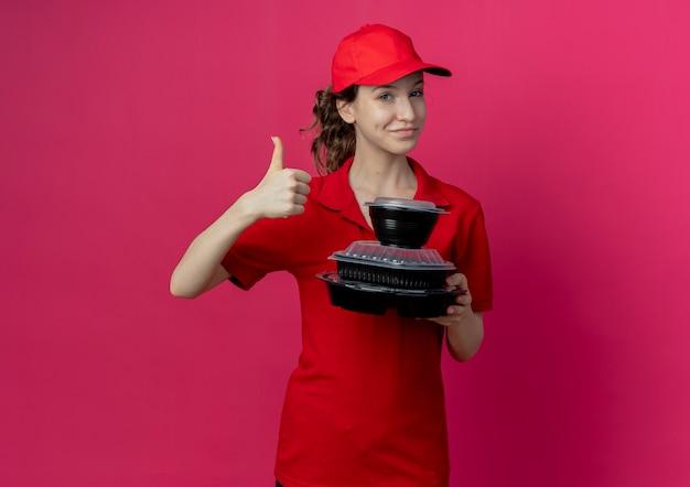 빨간 유니폼과 모자를 쓰고 음식 용기를 들고 엄지 손가락을 보여주는 젊은 예쁜 배달 소녀는 복사 공간이 진홍색 배경에 고립