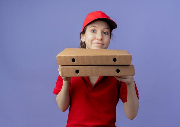 Довольная молодая симпатичная доставщица в красной форме и кепке, держащая упаковки пиццы, смотрящая в камеру, изолированную на фиолетовом фоне с копией пространства