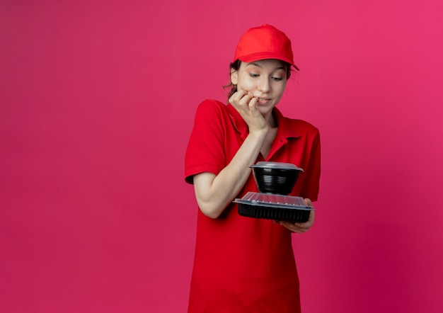 Pleased young pretty delivery girl wearing red uniform and cap holding and looking at food containers with hand on chin isolated on crimson background with copy space