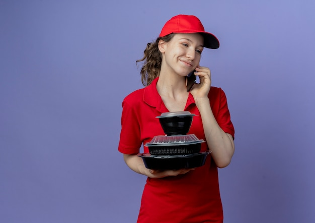 Pleased young pretty delivery girl wearing red uniform and cap looking at side holding food containers and talking on phone isolated on purple background with copy space
