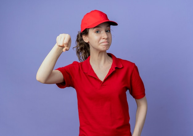 Pleased young pretty delivery girl wearing red uniform and cap pretend holding something isolated on purple background with copy space